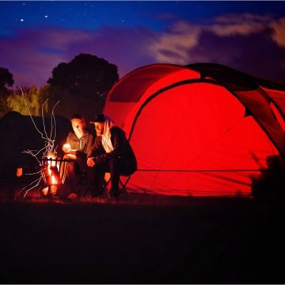 couple around camp fire with tent
